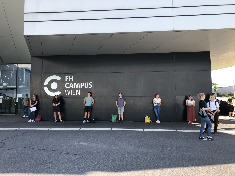 Studenten mit großem Abstand nebeneinander vor dem FH-Campus Hauptgebäude in Wien.