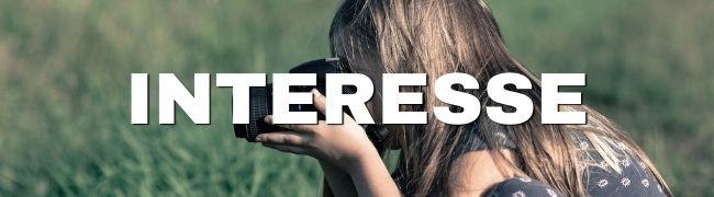 Mädchen mit Kamera in Wiese, Interesse